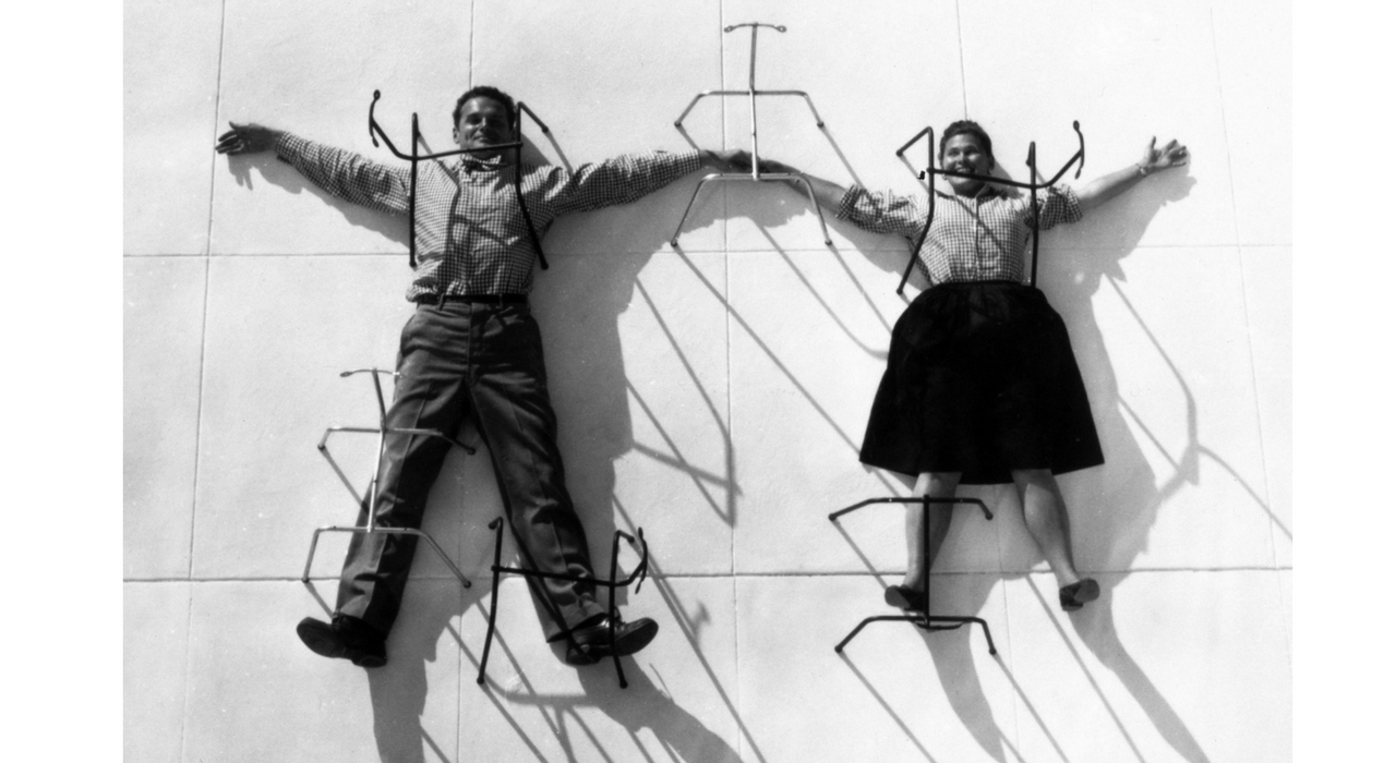 An Eames Celebration. Charles and Ray Eames posing with metal chair bases. ©Eames Office LLC