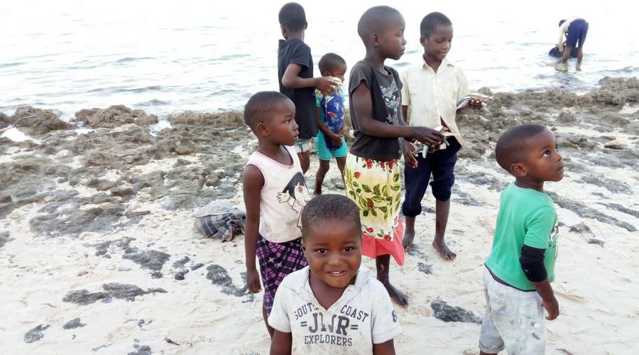 niños en la playa de Vilanculos, mientras sus madres compran pescado. Ellos iban cogiendo los pescaitos que encontraban por el suelo.