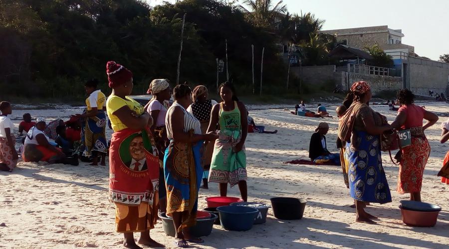 mujeres esperando a los pescadores para comprar sus pescados: especie de sardinas, calamares, ostras y peces manta.